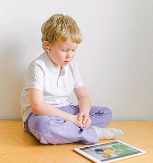 boy-in-white-polo-shirt-sitting-iPad